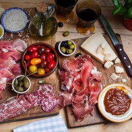 Photograph of a vibrant spread of charcuterie and fresh Italian antipasto.