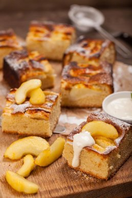 Photograph of fluffy, light apple cake with fresh apple slices and clotted cream.