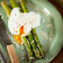Photograph of fresh asparagus and an oozing poached egg and shavings of parmesan.