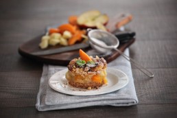 Photograph of apricot crumble with a dusting of icing sugar.