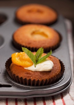 Photograph of freshly baked apricot muffins with thick Cornish cream.