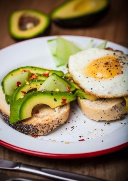Photograph of seasoned avocado and a fried egg on homemade poppy seed bread.