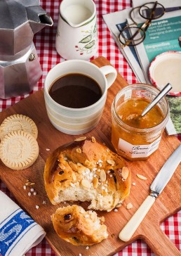 Photograph of a breakfast scene with freshly baked bread, marmalade, biscuits and coffee.
