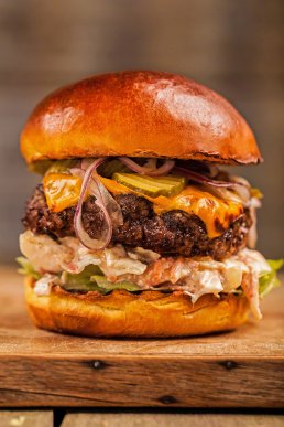 Photograph of a juicy gourmet beef burger with cheese, coleslaw, gherkins, onions and lettuce.