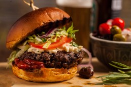 Photograph of a juicy beef burger oozing with relish, coleslaw, lettuce and tomato.