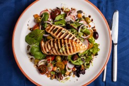 Photograph of grilled chicken breasts over a bed of crisp salad.