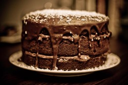 Photograph of a rich, oozing chocolate cake.