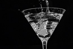 Photograph of an ice cube splashing into a crisp, refreshing cocktail.