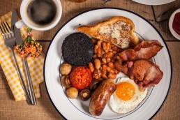 Photograph of a full cooked breakfast and coffee.