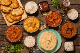 Photograph of a selection of colourful Indian curries and cuisine.