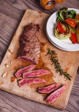 Photograph of a juicy sliced diaphragm steak.