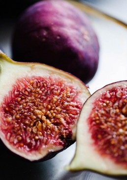 Photograph of colourful halved figs.