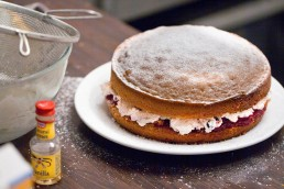 Photograph of a frosted cream and jam filled cake.