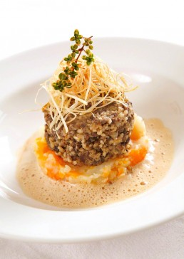 Photograph of gourmet haggis on a bed of neaps and potatoes.