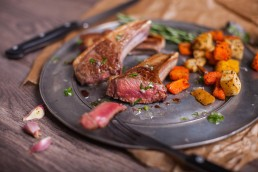 Photograph of a juicy lamb chump steak and roasted veg.