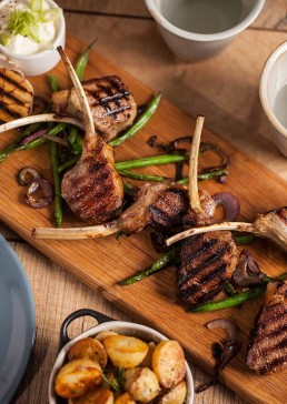 Photograph of an array of enticing lamb cutlets and green beans.