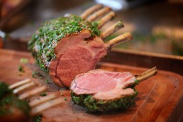 Photograph of a juicy, mint-encrusted lamb rack.