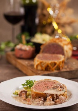 Photograph of a warming, packed meatloaf encroute.