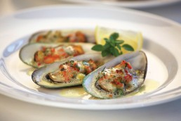 Photograph of fresh mussels in a white wine sauce.