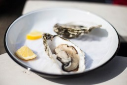 Photograph of freshly caught Scottish oysters with a squeeze of lemon juice.