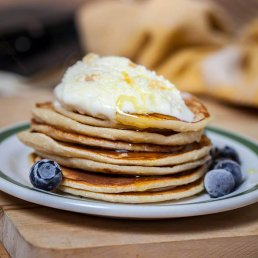 Photograph of fluffy pancakes with fresh blueberries.