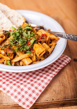 Photograph of a rich tomato pasta dish with crusty bread.