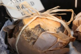 Photograph of freshly baked poppy seed bread wrapped in parchment paper.