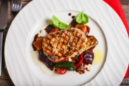 Photograph of a grilled pork ribeye steak on a bed of roasted vegetables.