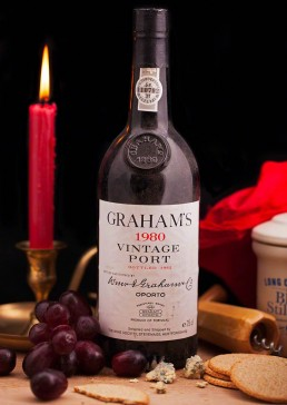 Photograph of a bottle of 1980 vintage port with cheese, biscuits and grapes.