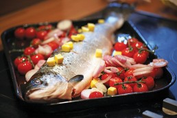 Photograph of an oven-ready salmon with tomatoes and onions.
