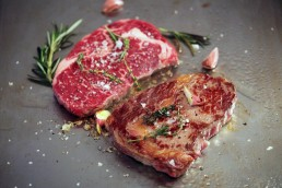 Photograph of two ribeye steaks cooking with herbs and garlic.