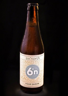 Product photograph of an ice cold, refreshing bottle of 6 Degrees North beer.
