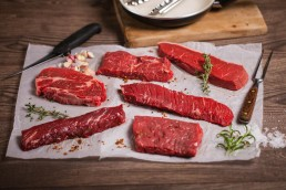 Photograph of a raw speciality steak selection.