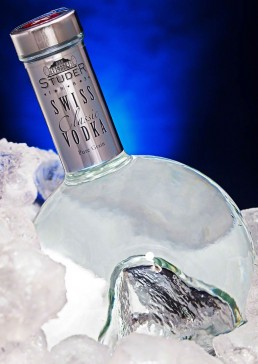 Photograph of a cold bottle of premium swiss vodka sitting in a bed of crushed ice.