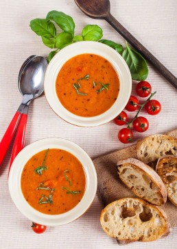 Photograph of fresh tomato soup with basil leaves and crusty bread.